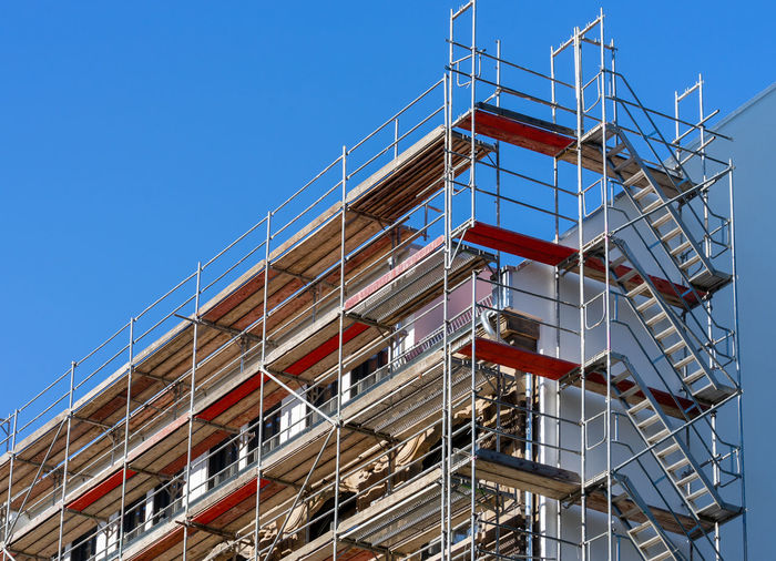 Low angle view of building construction site against blue sky