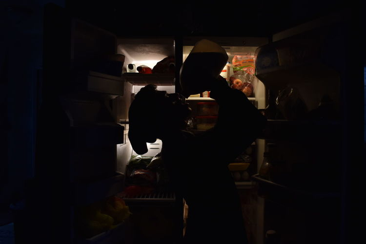 Side view of silhouette man drinking while standing by refrigerator at home