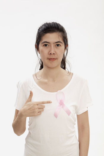 Portrait of woman pointing at breast cancer awareness ribbon against white background
