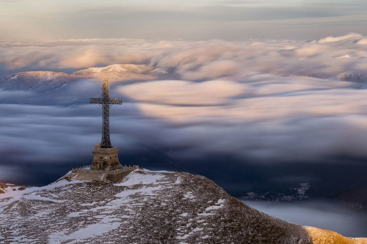 Religious cross on mountain by cloudscape