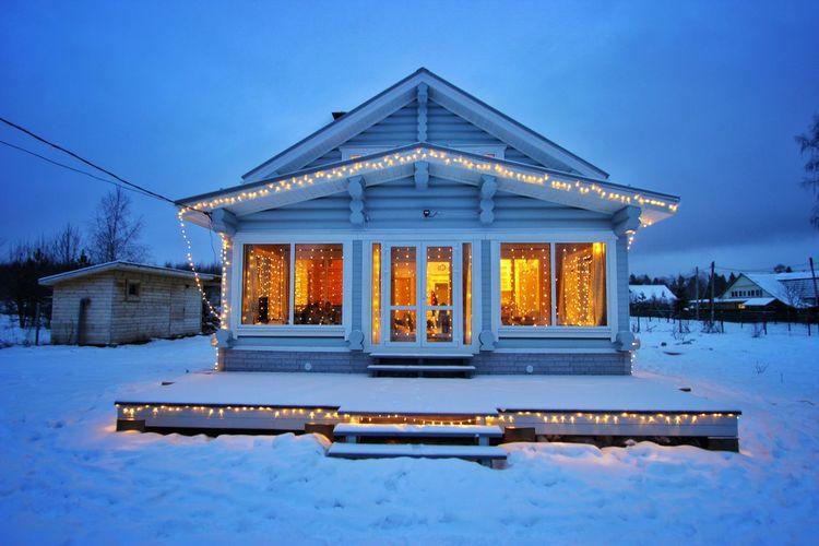 Snow covered house against blue sky