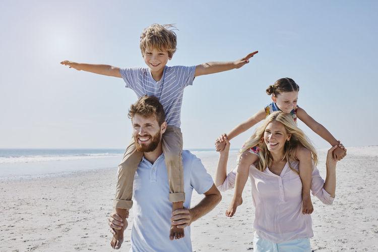 Full length of happy friends on beach against sky