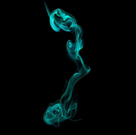 Close-up of green smoke against blue background