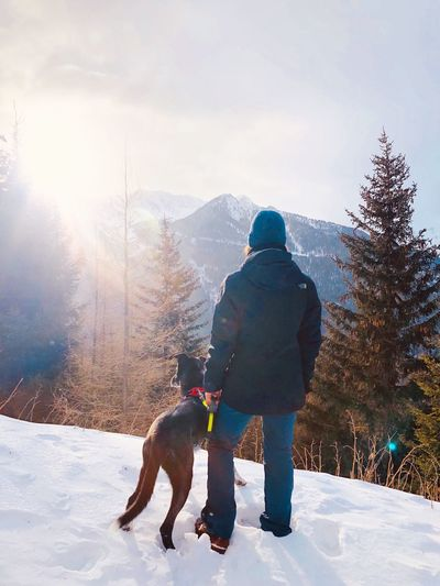 Woman with dog standing on snow against trees