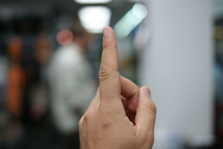 Cropped Hand Of Person Pointing Outdoors