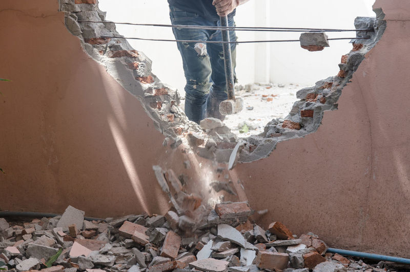 Midsection of construction worker demolishing wall with sledgehammer