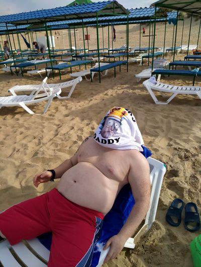 Full length of shirtless boy lying on sand at beach