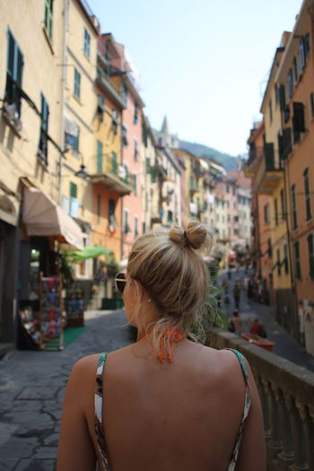 Woman in backless dress standing on street in city