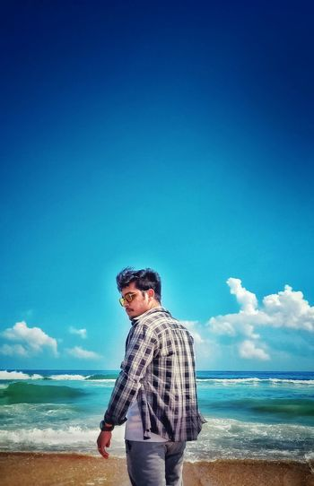 Young man standing at beach against blue sky