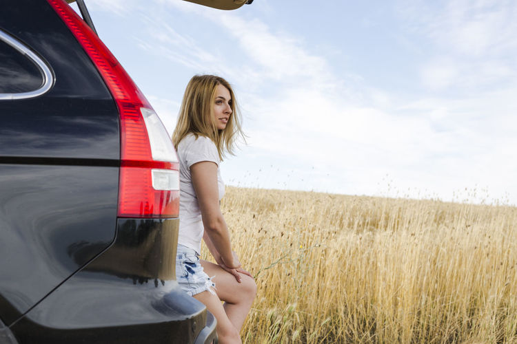 Side view of woman sitting on car trunk against sky