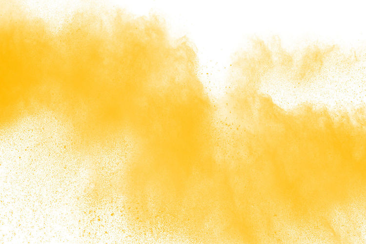 Defocused image of yellow powder paint against white background