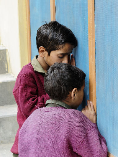 Two boys looking through a window Bonding Curious Day Family Friendship Him India Outdoors People Togetherness Two People