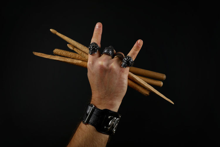 Cropped Hand Of Man Holding Sticks Over Black Background