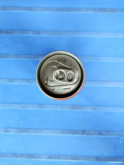Directly above shot of drink can on blue bench