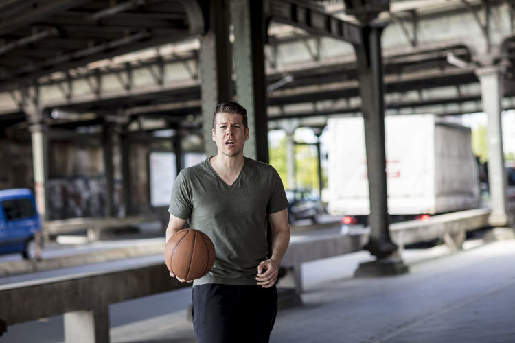 Portrait of young man with basketball standing on bridge