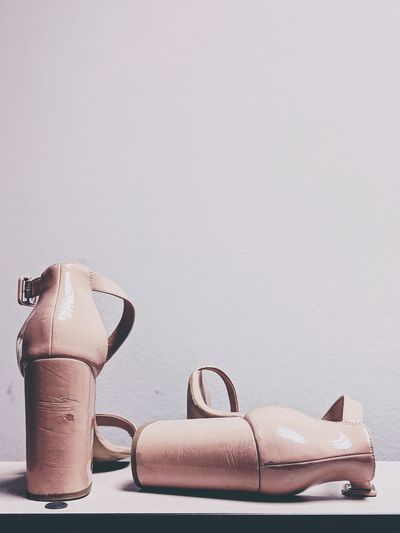 Close-up of shoes on table against white background