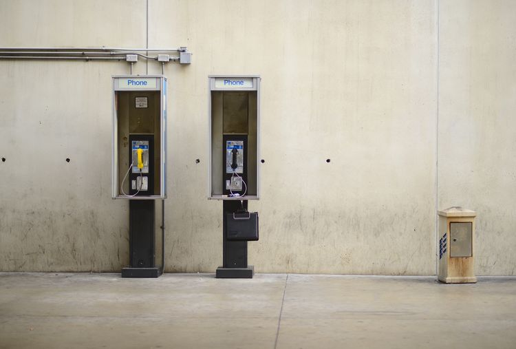 No further use these days Absence Airport Phon Building Exterior Built Structure Communication Concrete Wall Convenience Door Entrance No People Outdoors Pay Phone Phone Booth Phones Technology Telephone Telephone Booth Two Phones Wall - Building Feature