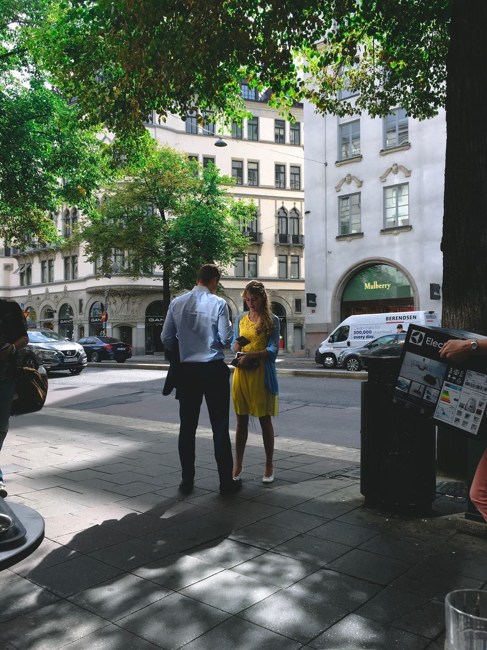 architecture, real people, building exterior, city, two people, built structure, full length, incidental people, tree, men, mode of transportation, transportation, women, day, motor vehicle, street, rear view, adult, plant, car, couple - relationship, outdoors