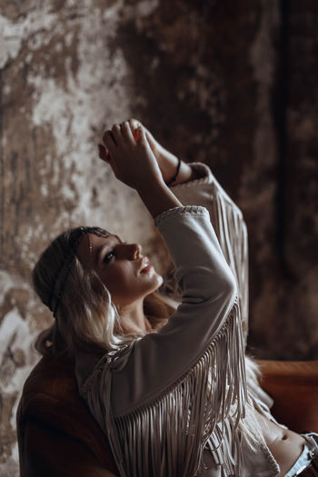 Young woman in beige boho style jacket posing against the background of a vintage wall