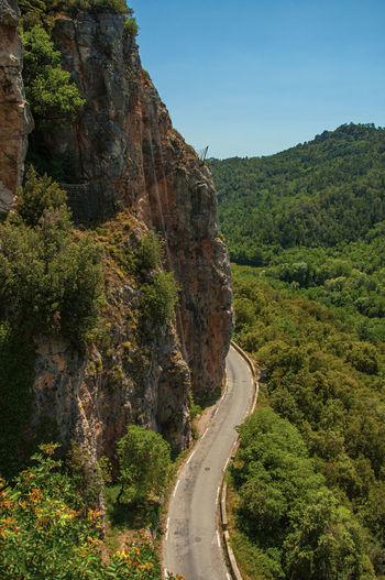 View of green valley and cliff, cut by road, near chateaudouble, in the french provence.