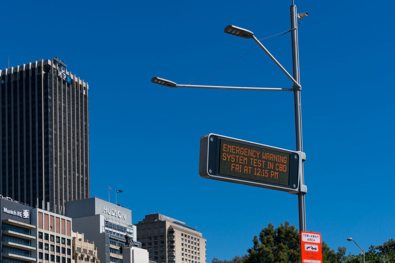 Low angle view of road sign by buildings against clear blue sky