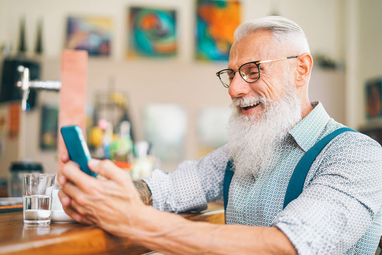 Senior man using mobile smartphone person Hipster Senior Adult Senior Man Beard Pensioner Retirement Happy Males  Glasses Indoors  Facial Hair Eyeglasses  Adult One Person Men Portrait Headshot Senior Men Sitting Gray Hair Table Business Glass