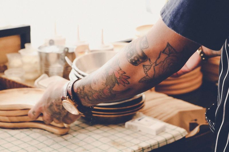 Close-Up Of Man With Tattoo On Hand Working In Kitchen