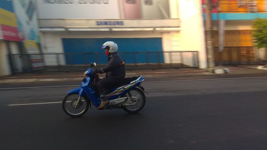 Man riding motor scooter on road