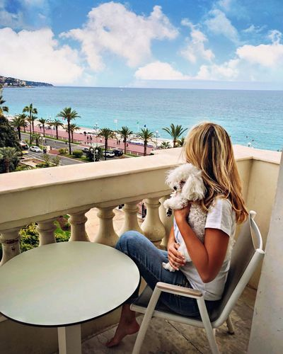 Woman with dog sitting on chair by sea against sky