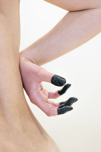 Close-up of woman holding hand over black background