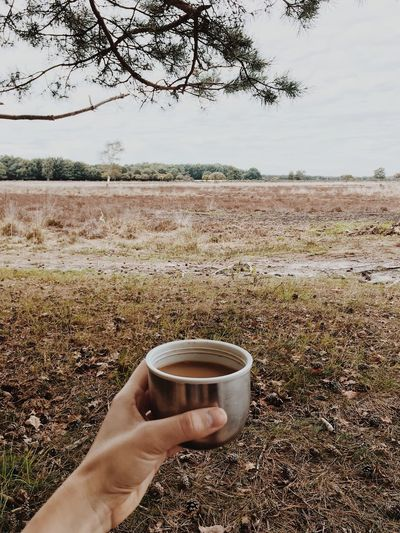 Hand holding coffee cup on field