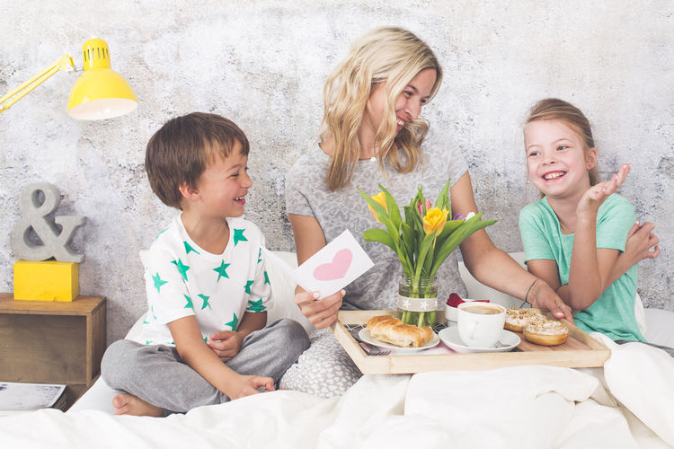 Cheerful mother with children having breakfast on bed