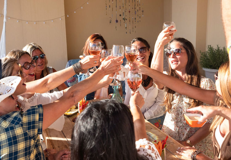 Female friends doing celebratory toast at building terrace