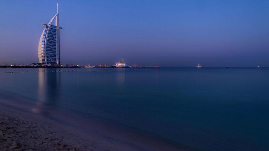 Burj Al Arab By Sea Against Sky During Sunrise In City