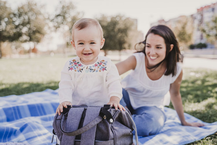 Mother looking at cute smiling baby daughter standing by backpack in park