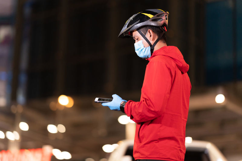 Side view of man using mobile phone at night