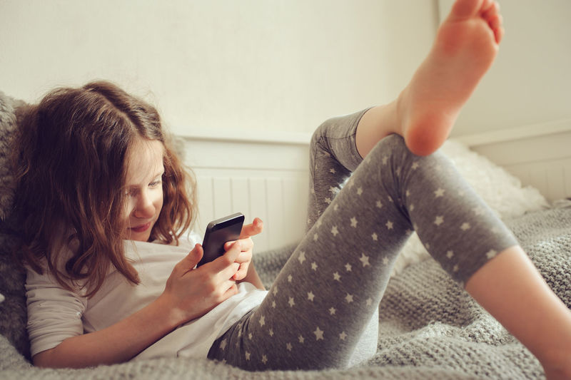 kid girl playing smartphone at home on the bed Indoors  Communication Lifestyles Wireless Technology Technology Portable Information Device Smart Phone Playing Childhood Child Girl Kid Preschooler Bed Nursery Authentic Moments Relaxing Cute Funny Learning Home Humanity Meets Technology