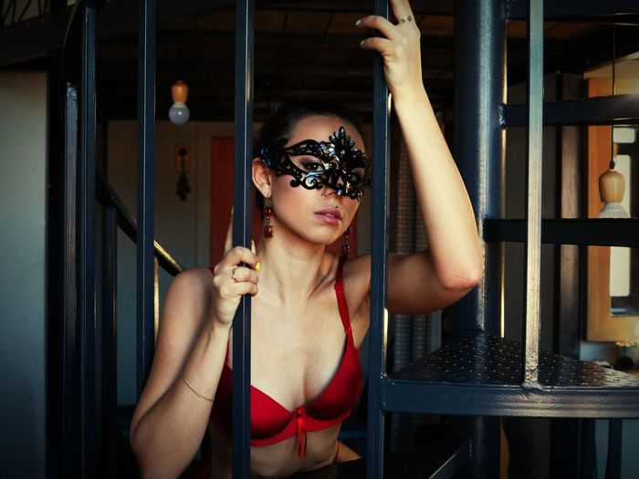 Portrait of sensuous young woman wearing eye mask by railing