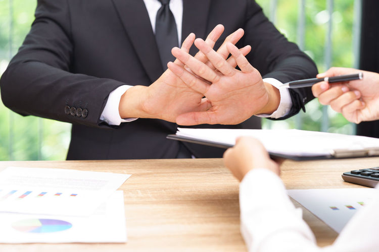Cropped Hands Of Person Giving Documents And Pen To Sign While Man Refusing Over Table