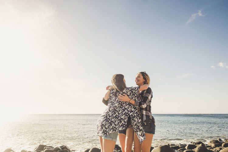Friends embracing at beach against sky