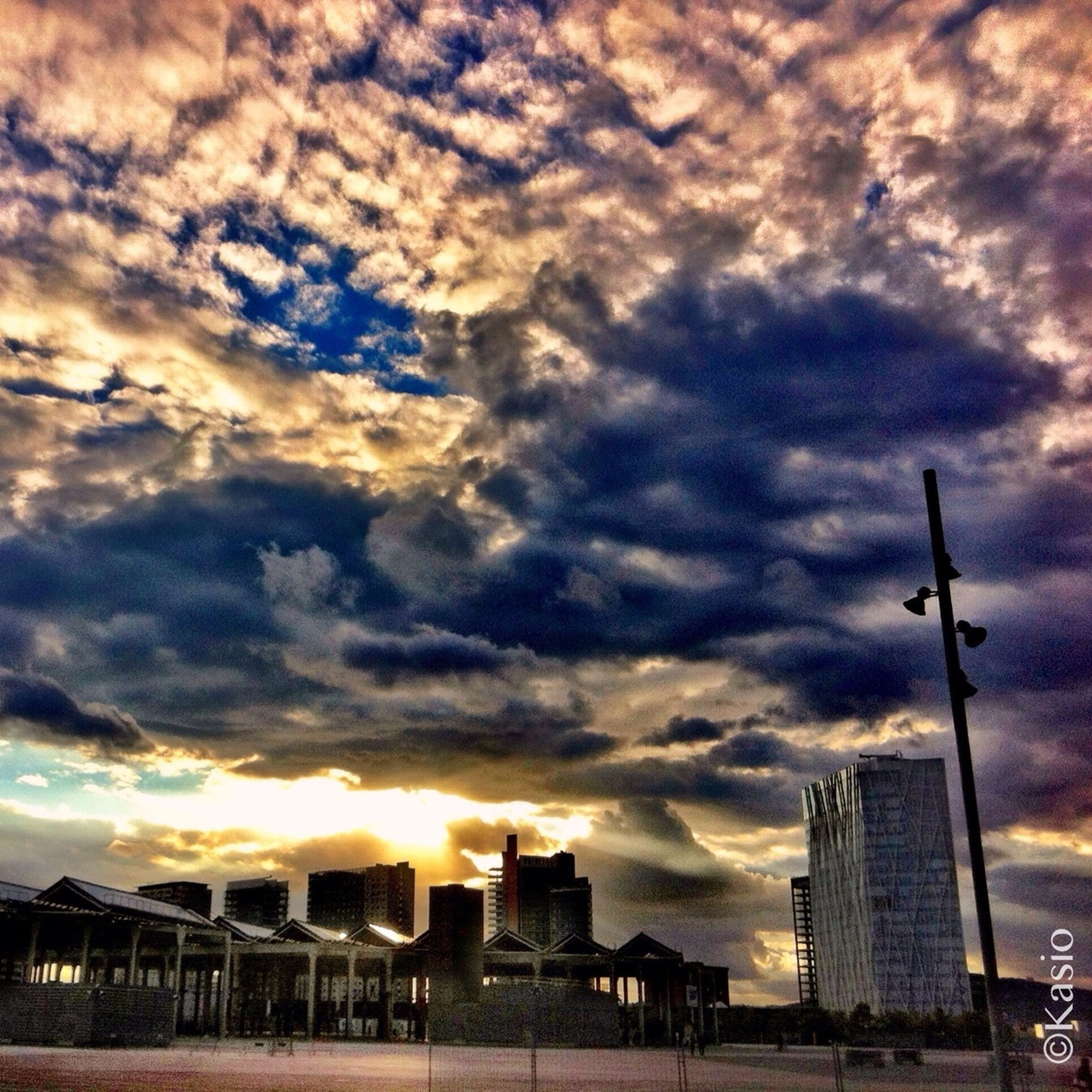building exterior, architecture, sky, cloud - sky, built structure, sunset, cloudy, city, weather, cloud, cityscape, crane - construction machinery, low angle view, modern, street light, skyscraper, overcast, building, development, silhouette