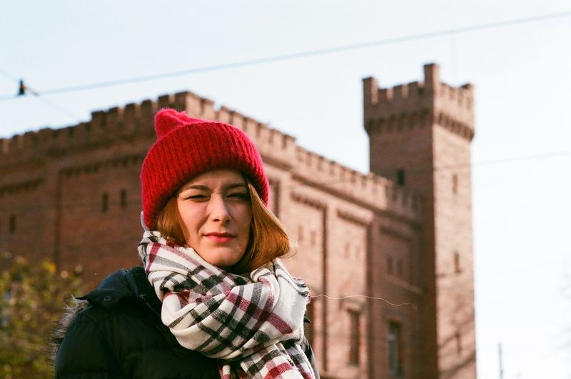 Portrait of young woman standing against castle