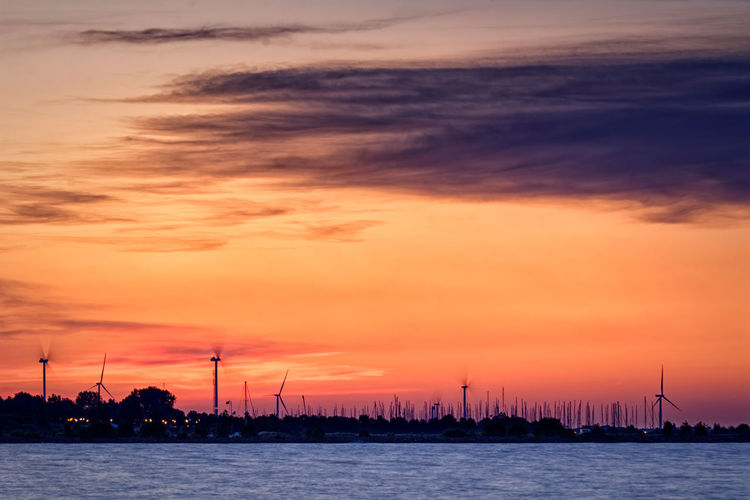 Silhouette sailboats in sea against dramatic sky during sunset