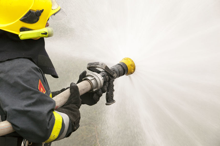 Firefighter in action Emergency FireFighting  Firefighter Action Danger Fire Fire Department Fire Hose Firefighter Fireman Helmet Holding Occupation Occupational Safety And Health Protective Glove Protective Workwear Reflective Clothing Rescue Spray Spraying Training Uniform Unrecognizable Person Water Working