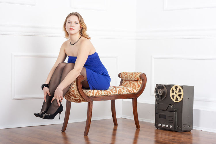 Portrait of sensuous young woman sitting on footstool at home