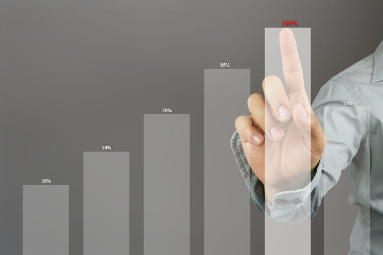 Digital composite image of businessman touching graph on device screen