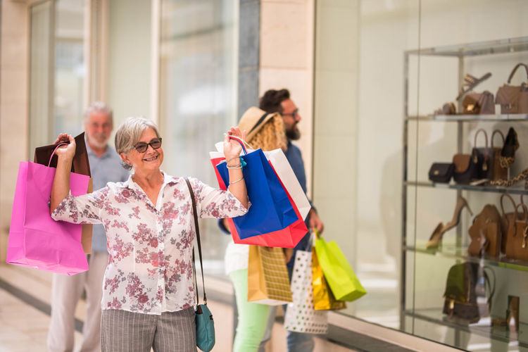 Smiling senior woman holding shopping bags outside store
