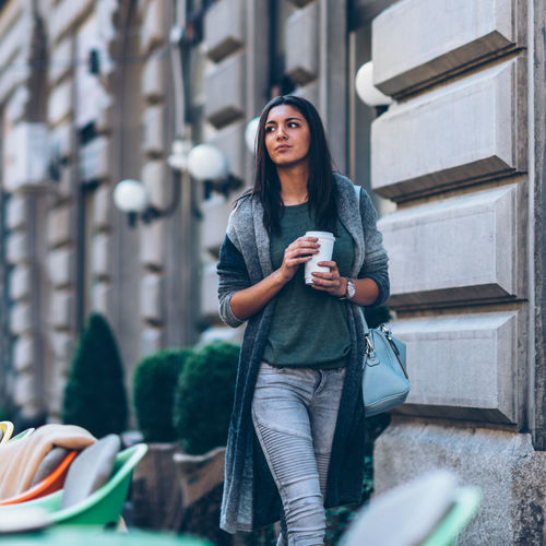 Young Woman Holding Disposable Cup While Walking In City
