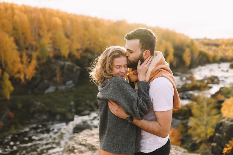 Happy people in love are travel hike in nature in the autumn forest. romantic trip to countryside