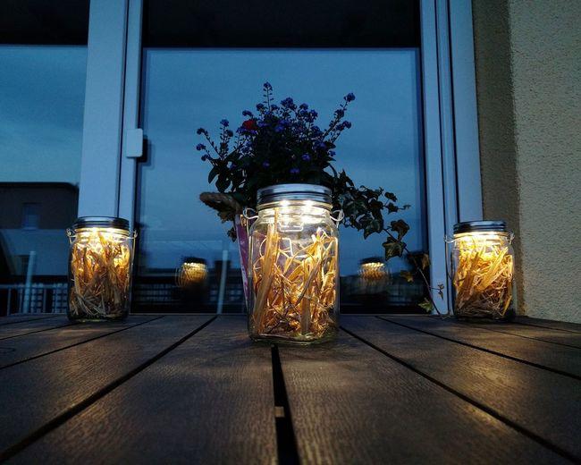 Illuminated flower vase on table against sky at night